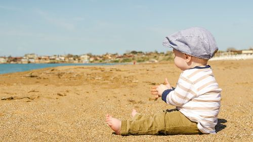 Beautiful Baby Boy Seating on Beach Sand Wallpaper
