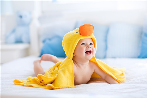 Smiling Cute Baby on Bed 4K Wallpaper