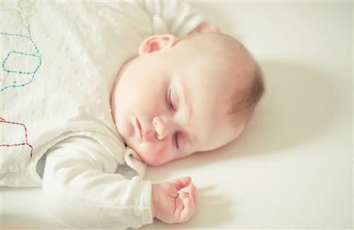 White Cute Baby Sleeping on Bed Wallpaper