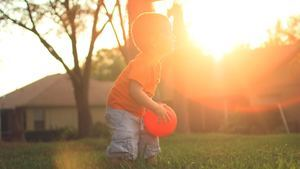 Cute Baby Boy Plaing with Ball in Garden Wallpaper