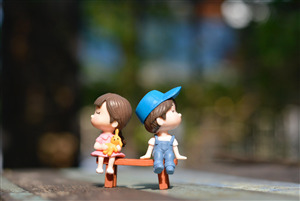 Toy Couple Sitting on Bench Love Wallpaper
